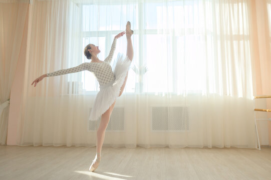 Beautiful ballerina in body and white tutu is training in a dance class. Young flexible dancer posing in pointe shoes.