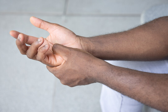 African man suffering from wrist or hand pain, sick black man with CTS, wrist pain, trigger finger, bone arthritis, gout symptoms, De quervain's disease, joint sickness, health care or pain concept