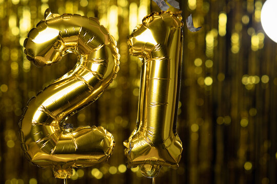 Golden number 21 twenty one made from an inflatable balloon, on a yellow background. One of the complete set of numbers. The concept of birthday, anniversary, date