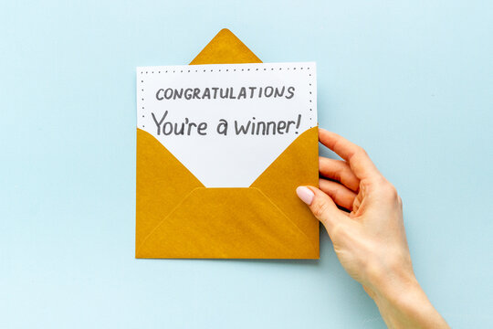 Female hand holds envelope with card You are a winner. Congratulations award letter