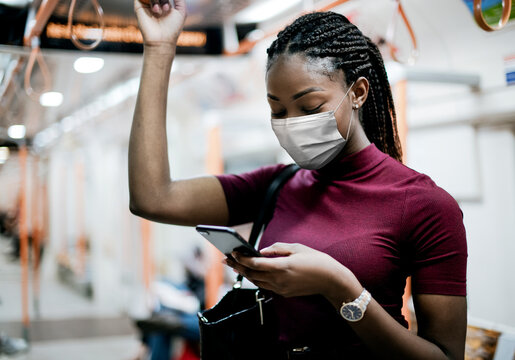 African American woman wearing mask on the bus while using public transportation in the new normal