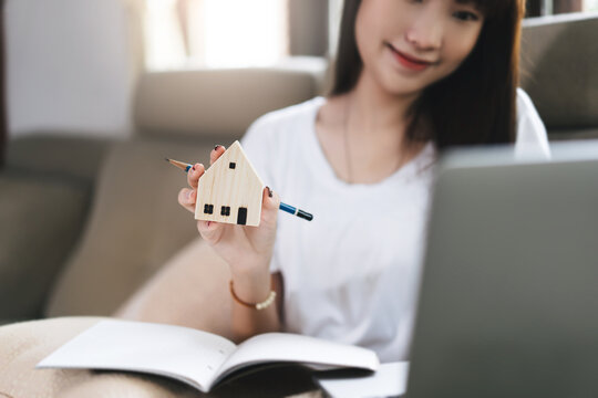 Asian student woman hand holding wooden house model.