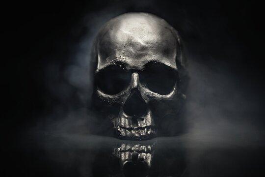 Spooky dark black skull aginast dark background