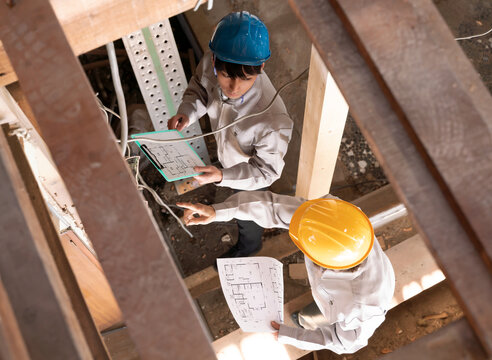 住宅建築現場で働く人々 スケルトンリフォーム 打ち合わせ 見下ろす 電気工事