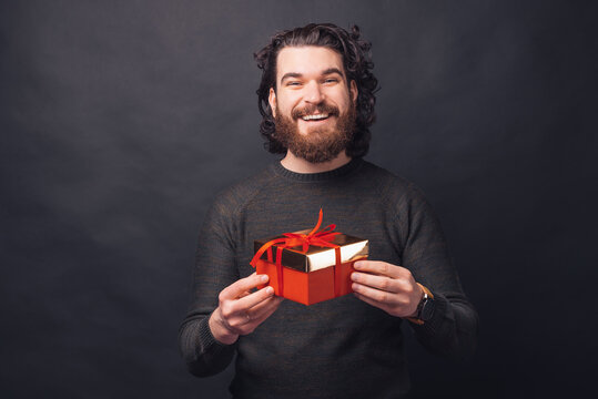 Portrait of joyful bearded man holding red gift box over black background.