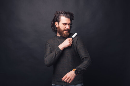 Photo of handsome man removing pet hair from sweater.