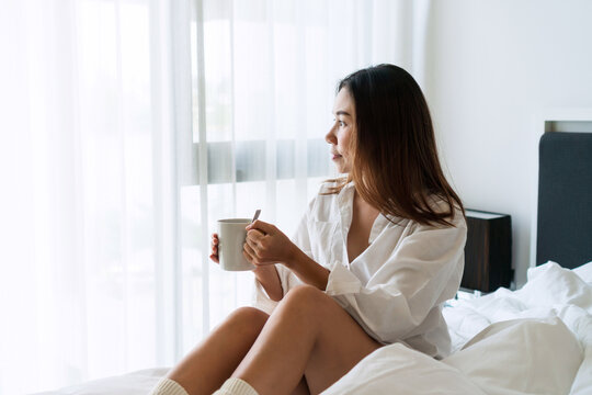 Young beautiful brunette hair girl in white shirt pajamas drinking coffee while sitting on the bed in the morning.