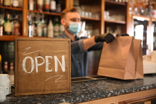 OPEN sign and blurred view of waiter with takeout orders on background. Food service during coronavirus quarantine