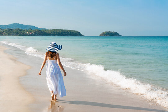 Happy traveler young Asian girl in white dress enjoys at tropical beach on vacation. Summer on beach concept.
