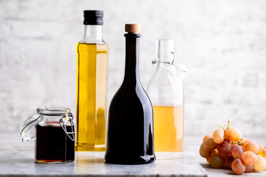 Original glass bottles with different vinegar on a marble table against a background of a white brick wall. Copy space.