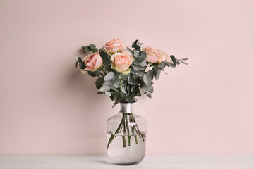 Printed kitchen splashbacks Roses Vase with bouquet of beautiful roses on white wooden table near beige wall