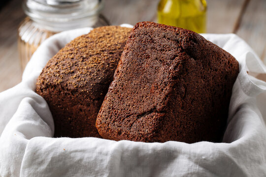 Side view on two loafs of rye bread in a basket with napkin