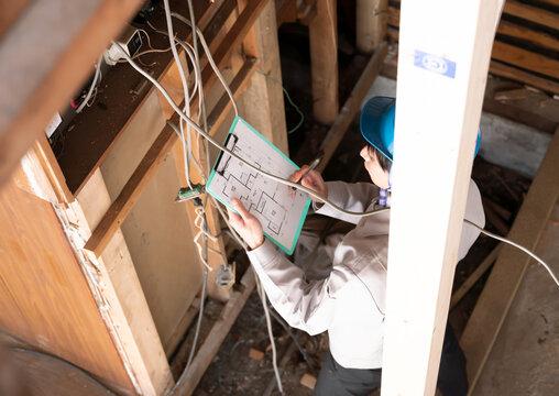 住宅 スケルトンリフォーム 解体現場で分電盤を調査するビジネスマン