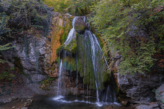 Jur-Jur waterfall in the Crimea. Streams of water flow down a steep stone ledge covered with green and yellow moss. Horizontal image.