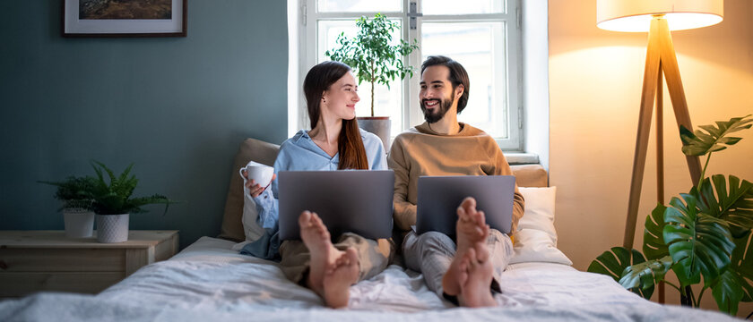 Young couple using laptops on bed indoors, home office concept.