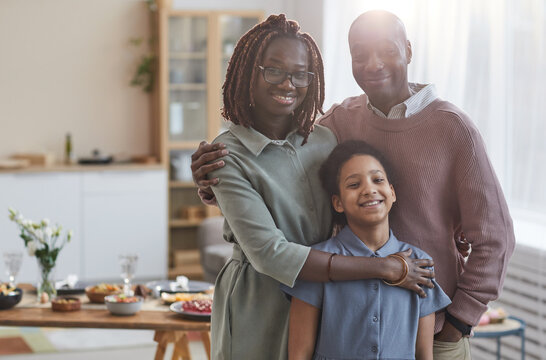 Portrait of happy African-American family looking at camera while posing indoors in cozy home interior with dinner table in background, copy space