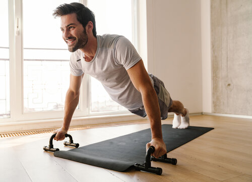 Joyful athletic man doing exercise with push-up stops while working out