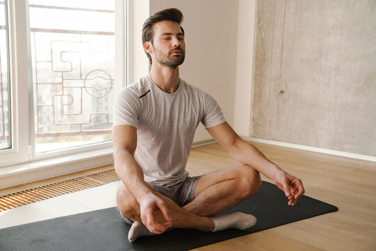 Concentrated athletic man meditating after workout at home