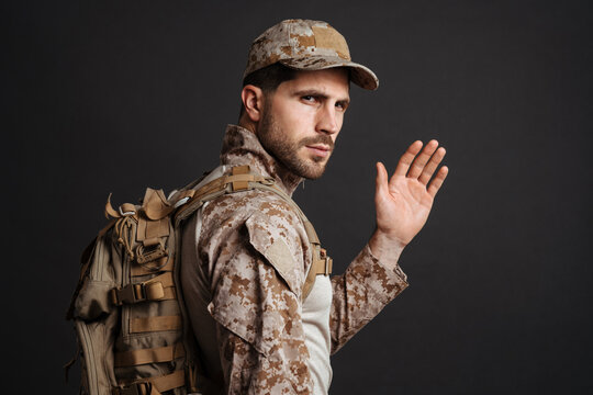 Confident masculine military man waving hand while posing with backpack