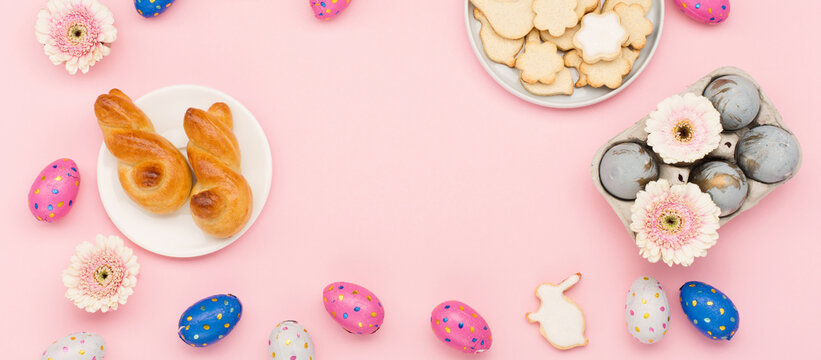 Homemade Easter bunny buns, sugar cookies, chocolate eggs, flowers on pastel pink background. Festive Easter breakfast concept.