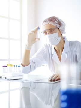 Professional female scientist in protective eyeglasses researching tube with reagents in sunny laboratory. Medicine and science researching
