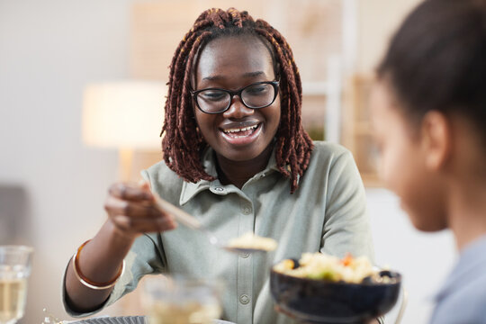 Portrait of modern African-American family enjoying dinner together at home, focus on smiling young woman sharing homemade meal with daughter