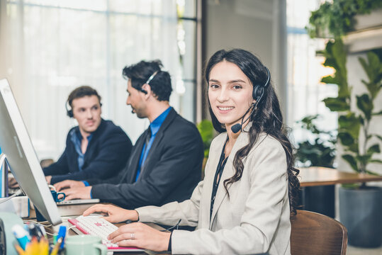 Beautiful Caucasion women on Tele Marketing representative or sales agents sitting at workplace wearing headset use computer, focus on call center. Hand holding cup of coffee.