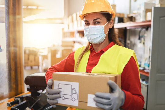 Hispanic warehouse worker woman holding delivery box while wearing safety mask - Focus on face