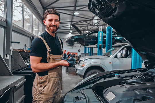 After the work is done. A confident young man in uniform wiping his hands with a rag and smiling while standing in the workshop with a car on the background.
