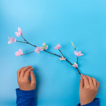kids holds an easy easter tree branch with flowers, spring craft for kids,