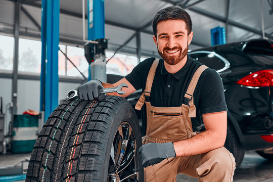 A technician in workwear, holding a wrench and a car tire in tire fitting.