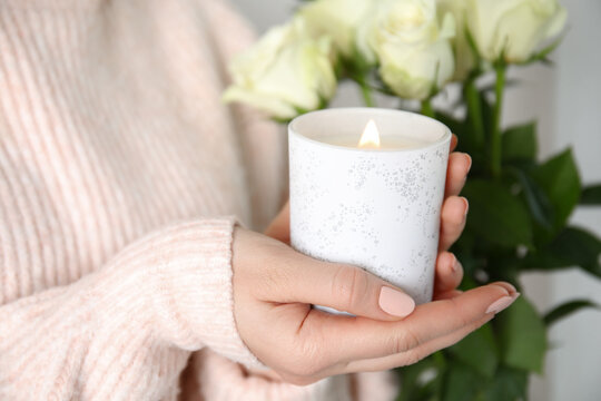 Woman holding burning candle with wooden wick, closeup