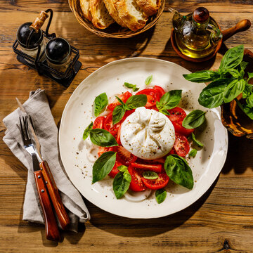 Salad with Tomatoes and Burrata cheese with basil and olive oil on wooden background