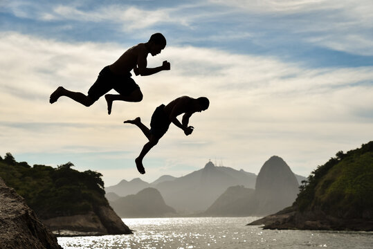 Silhouette of Two Boys Jumping Into the Ocean With Sugarloaf Mountain and Corcovado on Background, in Niteroi, Rio de Janeiro, Brazil