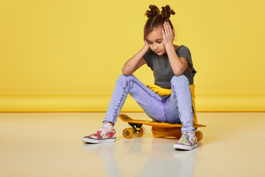 tired upset little child girl sitting on skateboard on yellow studio background