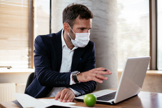 Young businessman with a mask working in his office on laptop. COVID - 19 virus protection