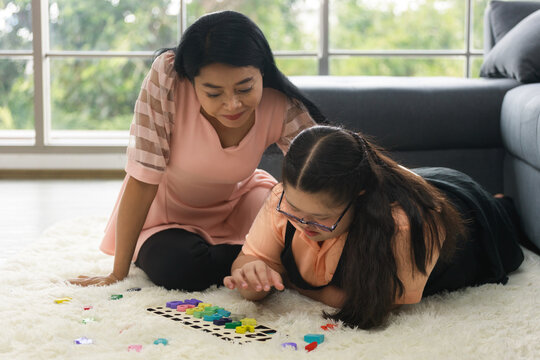 young girl with autism is practicing playing with toys on the floor at home with his mother. Autistic young students are learning with teachers.
