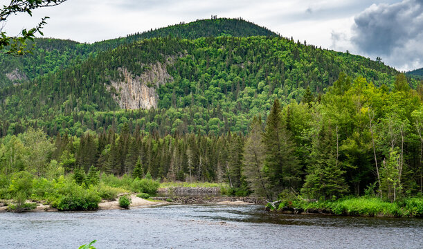 Huge cliffs with green trees everywhere on it facing two dams made by beavers near Fjords du Saguenay in Quebec Province, Canada