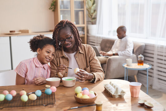 Portrait of loving African-American mother and daughter painting Easter eggs together while sitting at wooden table in cozy home interior and enjoying DIY art, copy space