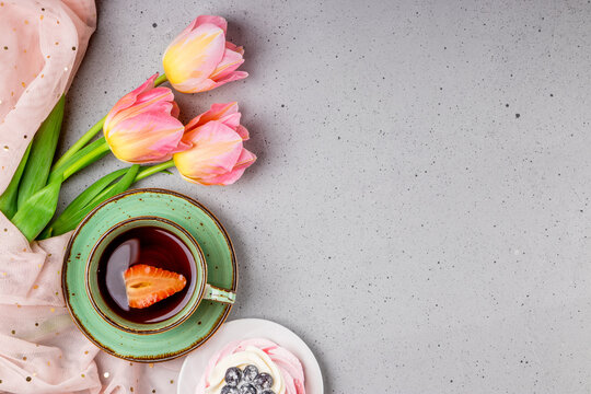 Cup of tea with strawberries, Pavlova cake and pink tulips on gray background top view, photo with copyspace
