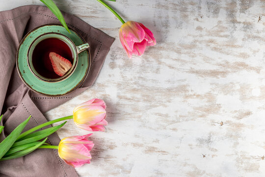 Cup of tea with strawberries and pink tulips on white wooden background top view, photo with copyspace