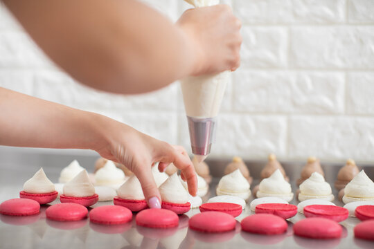 Step by step process of making macarons in confectionery shop. Close up horizontal shot of macarons shells in rows and hands of female pastry chef, filling it with white cream ganache