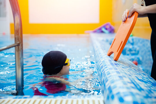 Swimming trainer woman instructing kid girl in pool, concept swimmer children