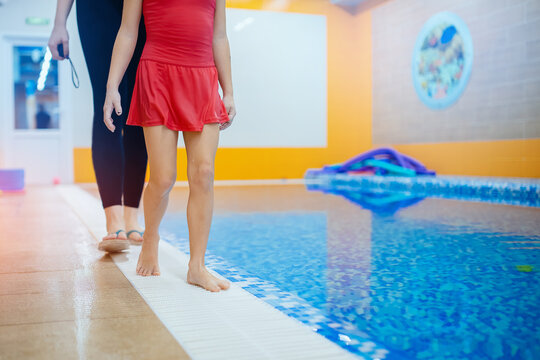 Girl kid learning to swim with women coach at swimming pool