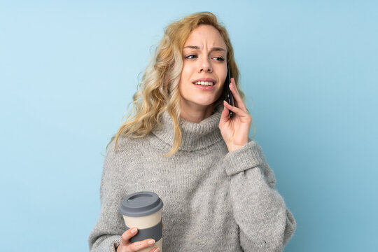 Young blonde woman wearing a sweater isolated on blue background holding coffee to take away and a mobile