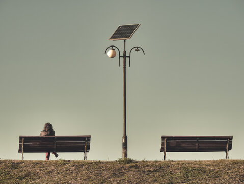 Lonely woman sitting on a bench next to a light pole. Two benches with a solar panel lamp post in the middle