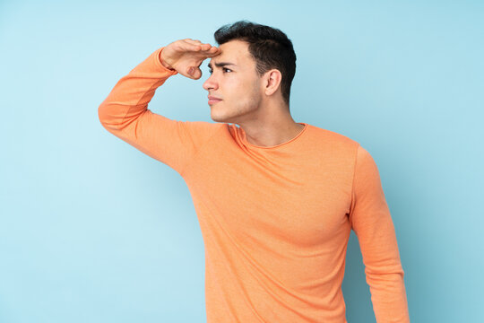 Young caucasian handsome man isolated on blue background looking far away with hand to look something