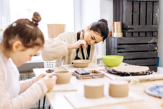 Two sisters decorate a clay plate before firing in a pottery studio, Children with brushes and pottery