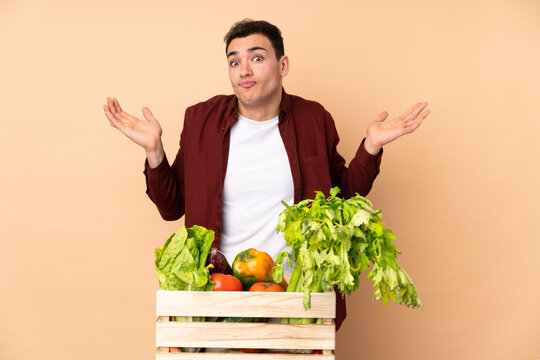 Farmer with freshly picked vegetables in a box isolated on beige background making doubts gesture