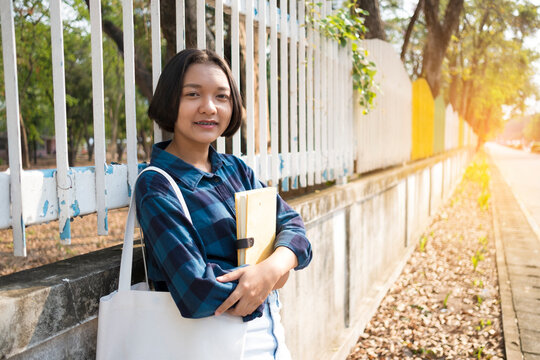 Portrait Of Teenage Girl With Book Standing Outdoor